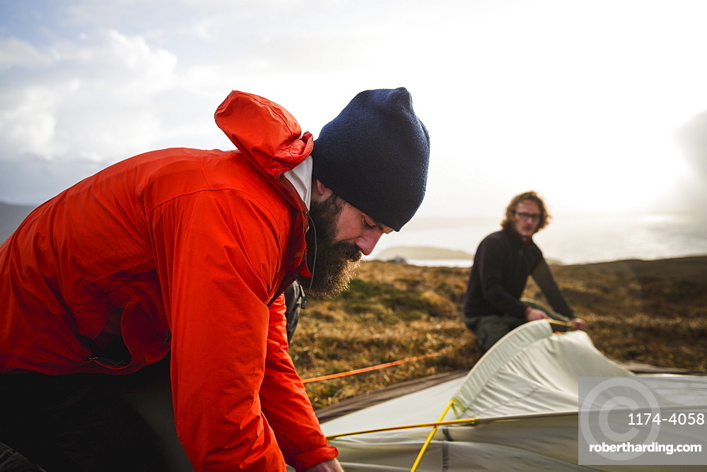 Two men holding and putting up a small tent in open space. Wild camping, Scotland, United Kingdom