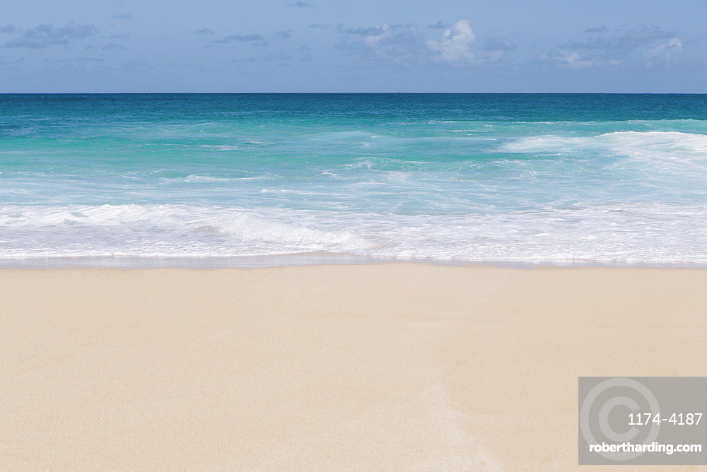 Vivid turquoise waters and waves breaking on the beach.