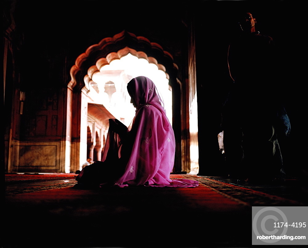 Woman wearing a pink veil and sari sitting on the floor covered with carpet. Scalloped archway. Deep shadow, India