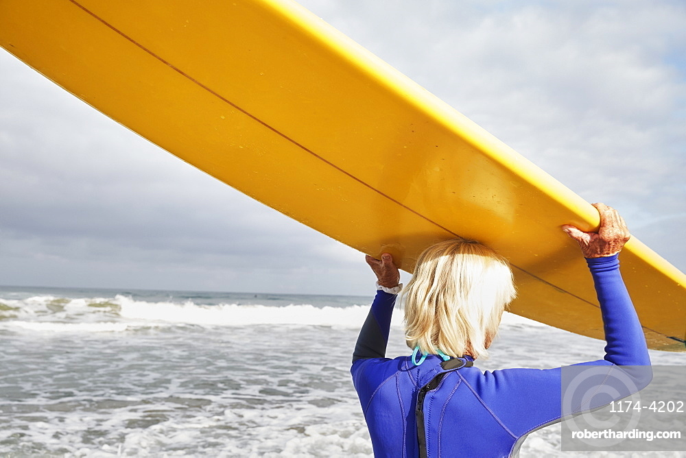 Senior woman on a beach, wearing a wetsuit and carrying a surfboard on her head, United States of America
