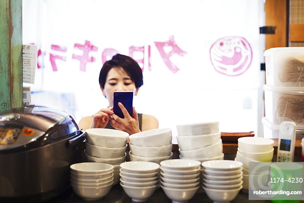 A woman using a smart phone at a noodle shop, Japan