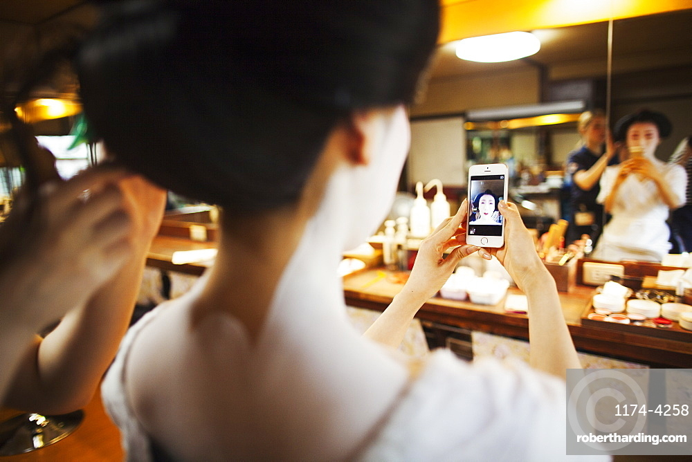 A geisha or maiko with a hair and make up artist creating the traditional hair style and make up. Woman making a selfie in the mirror with a smart phone, Japan