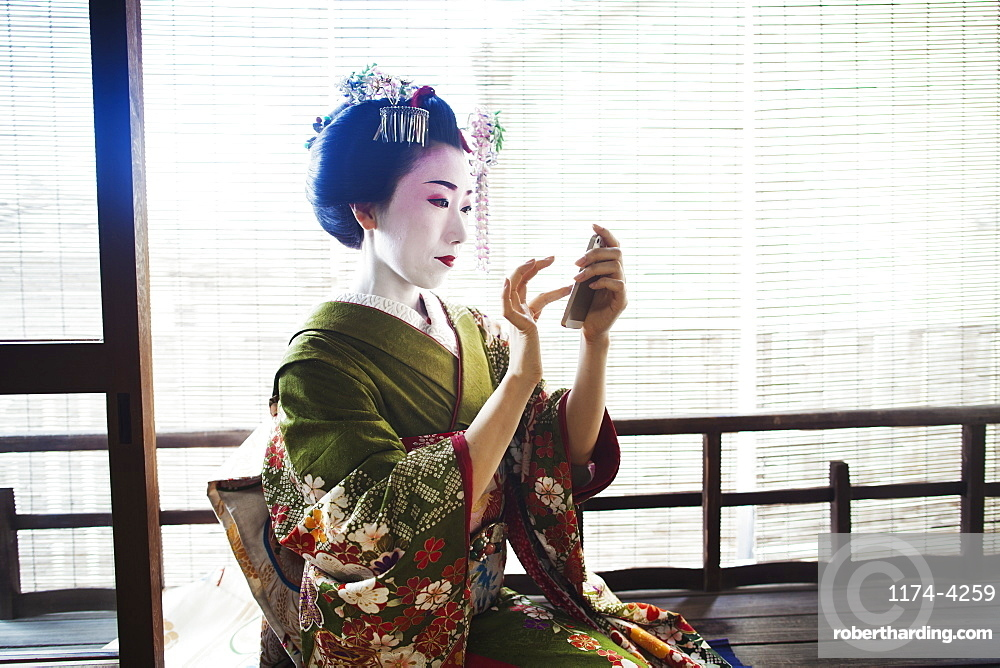 A woman dressed in the traditional geisha style, wearing a kimono and obi, with an elaborate hairstyle and floral hair clips, with white face makeup with bright red lips and dark eyes taking a selfie of herself, Japan