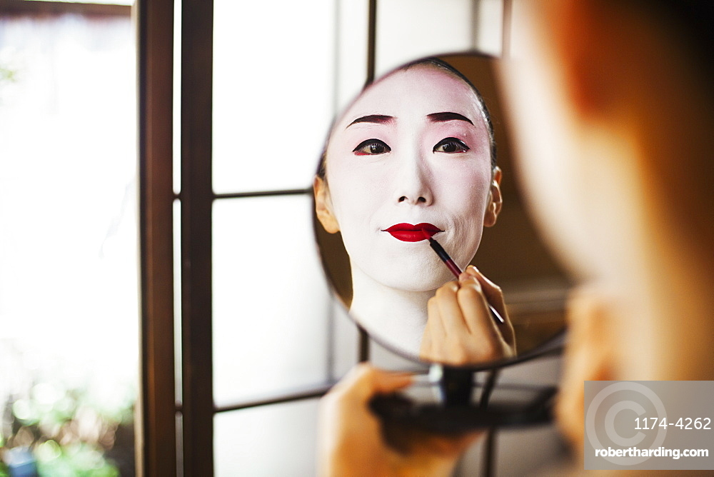 Geisha woman with traditional white face makeup applying bright red lipstick with a brush, using a mirror, Japan