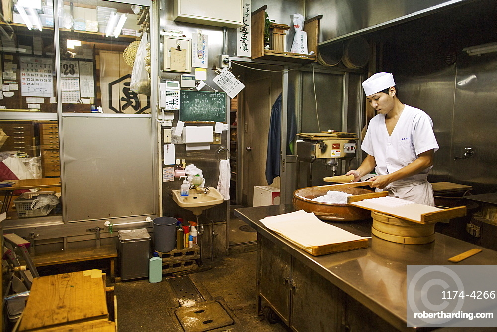 A small artisan producer of wagashi. A man mixing a large bowl of ingredients and pressing the mixed dough into moulds in a commercial kitchen, Japan