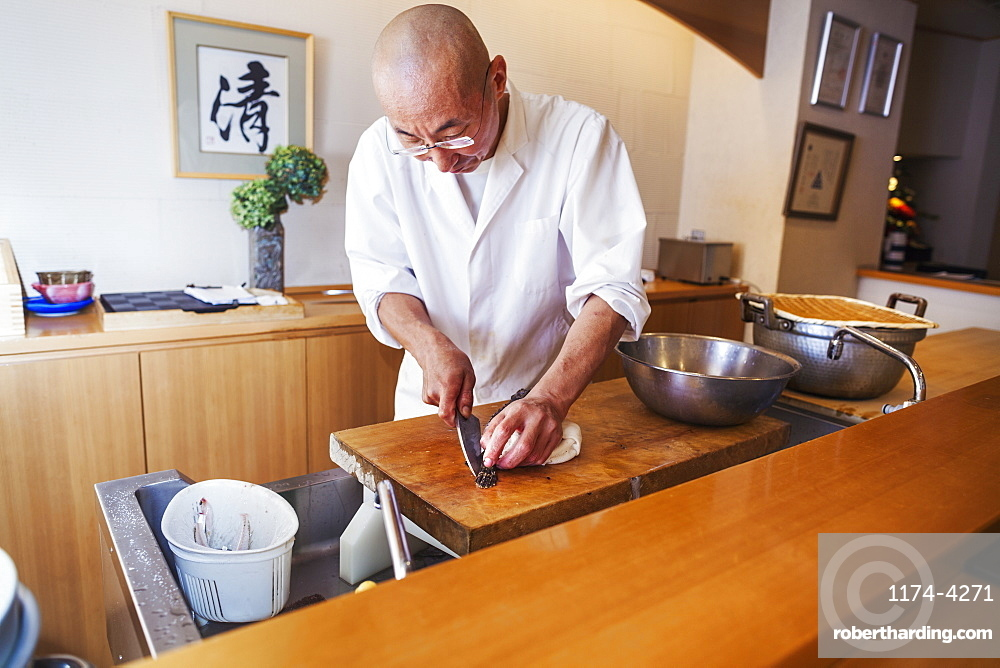A chef working in a small commercial kitchen, an itamae or master chef slicing fish with a large knife for making sushi, Japan