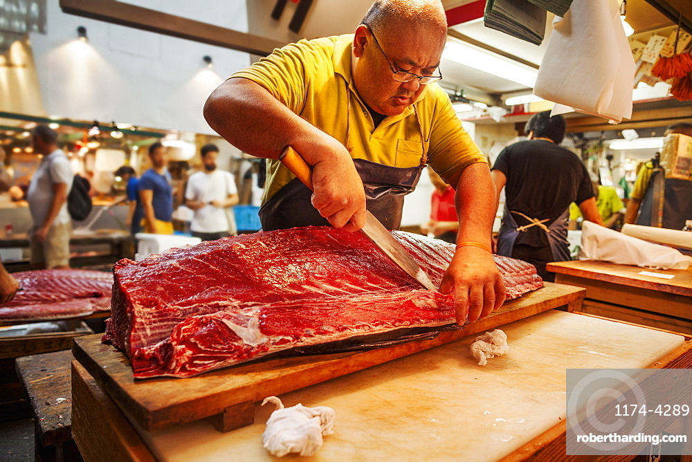 A traditional fresh fish market in Tokyo. A fishmonger working filleting a large fish on a slab. People in the background, Japan