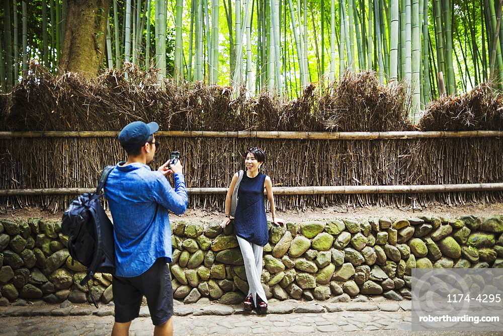 A man taking a photograph of a woman by a fence around woodland, Japan