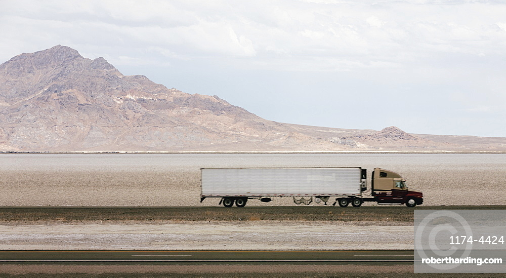 Lorry driving on a road through a desert landscape with mountains in the background.