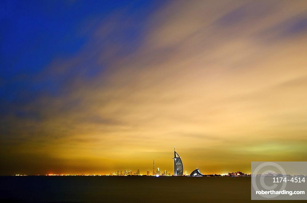 Cityscape of Dubai, United Arab Emirates at dusk with illuminated Burj Al Arab skyscraper in the distance, Dubai, United Arab Emirates