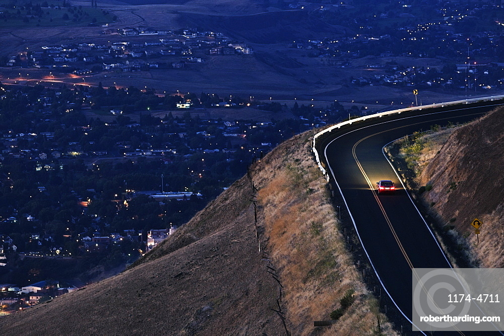 A view looking down on a car moving on a highway almost at dark near Clarkston, Washington, United States of America