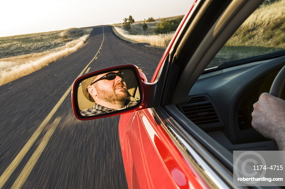 View in the rear view drivers mirror of a Caucasian male driving a car on a road trip in eastern Washington State, United States of America