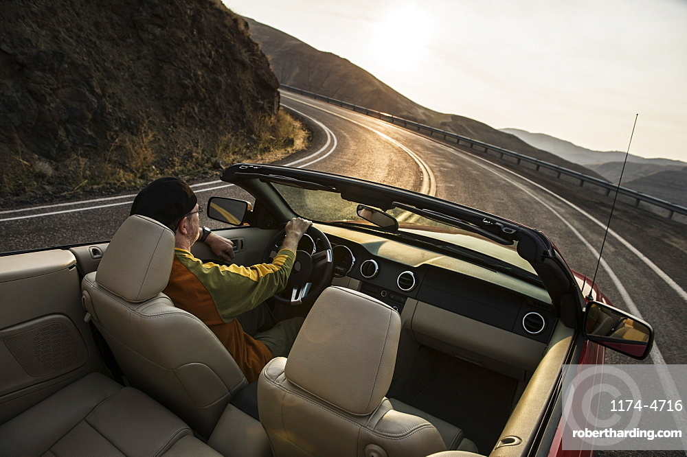 A view from behind of a Caucasian male driving a convertible sports car in eastern Washington State, United States of America