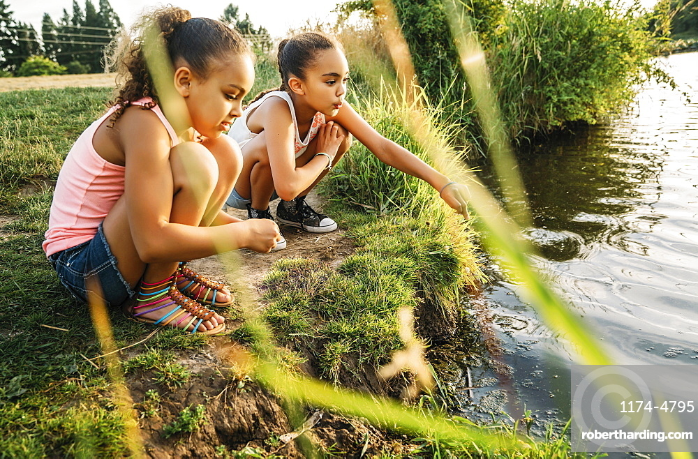 Girls playing by the edge of a lake in a park, United States of America