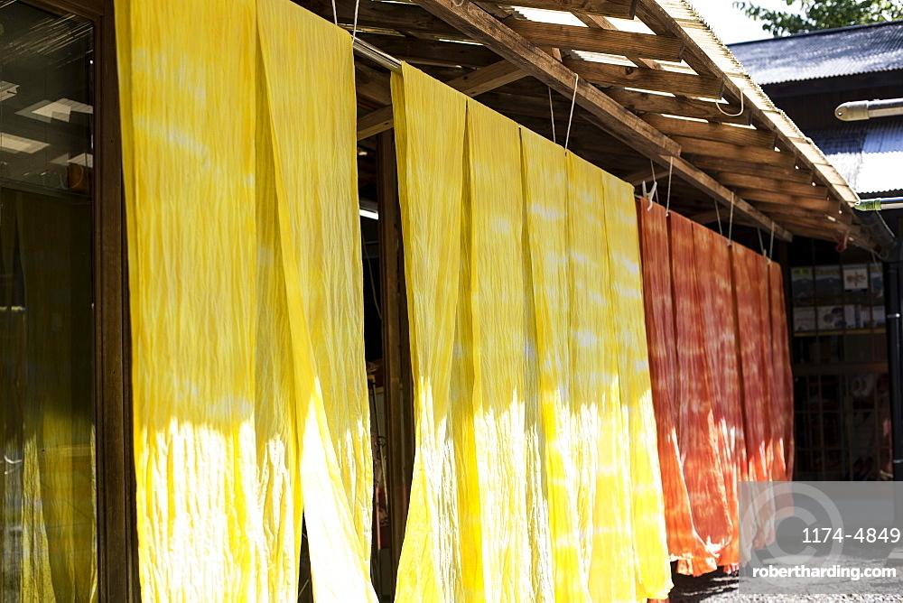 Freshly dyed bright yellow and orange fabric hanging outside a textile plant dye workshop, Kyushu, Japan