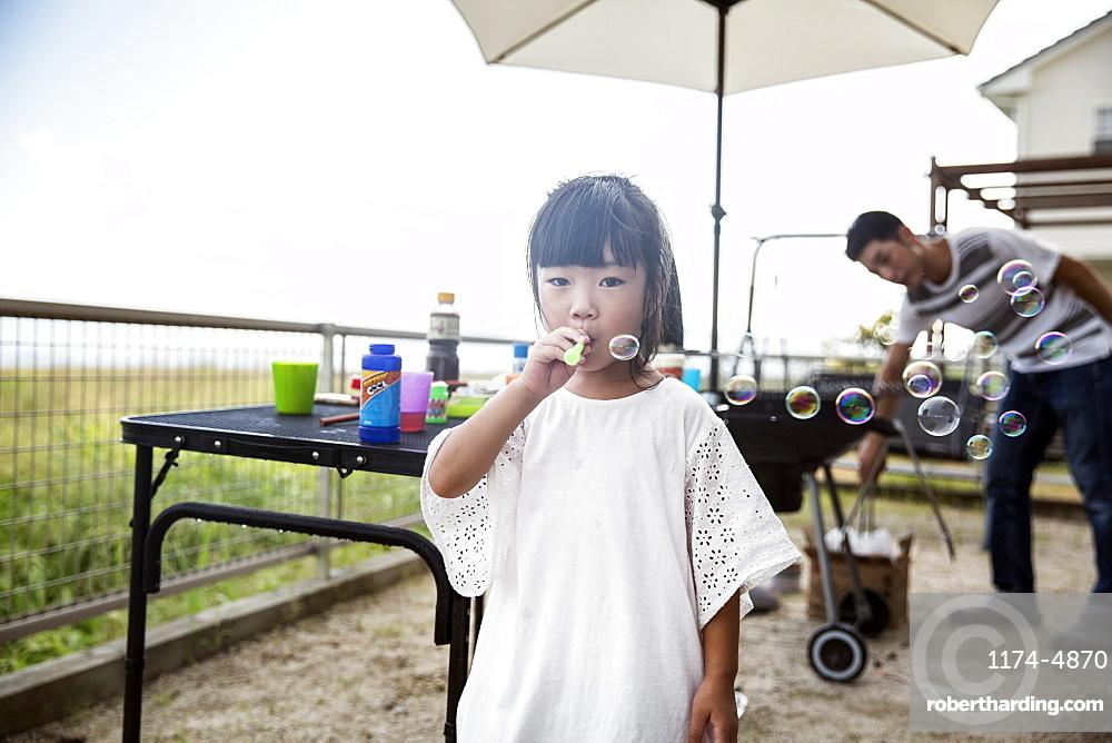 Portrait of Japanese girl wearing white shirt blowing soap bubbles, Kyushu, Japan