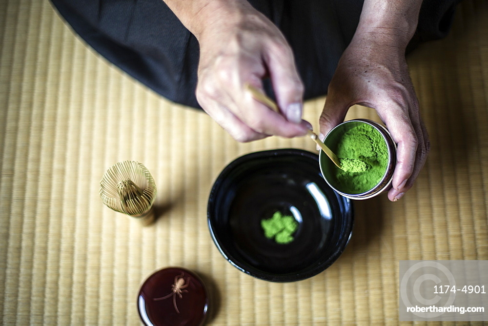High angle close up of traditional Japanese Tea Ceremony, man spooning green Matcha tea powder into bowl, Kyushu, Japan