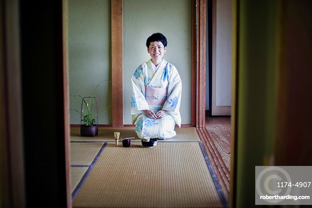 Japanese woman wearing traditional white kimono with blue floral pattern kneeling on tatami mat during tea ceremony, Kyushu, Japan