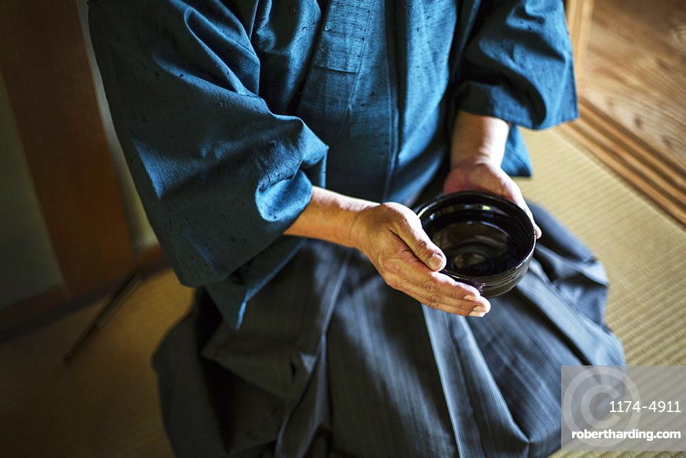 High angle close up of Japanese man wearing kimono holding tea bowl during tea ceremony, Kyushu, Japan