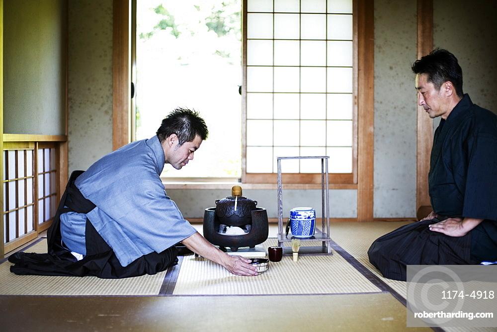 Two Japanese men wearing traditional kimonos kneeling on floor during tea ceremony, Kyushu, Japan