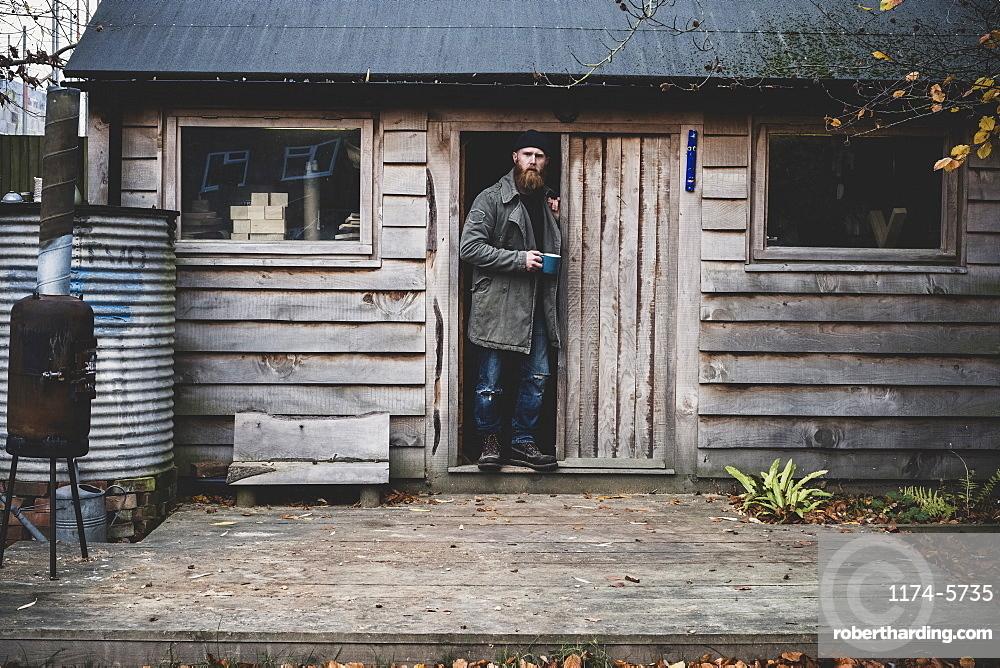 Bearded man standing in doorway of wooden workshop, holding blue mug, looking at camera, Berkshire, England