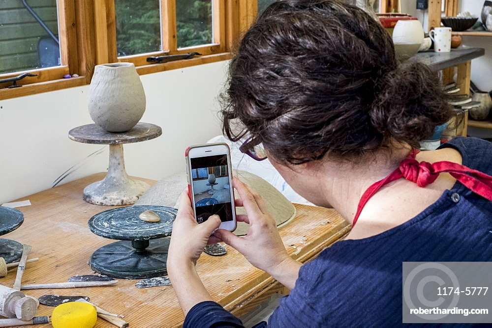 Over the shoulder view of woman sitting in her ceramics workshop, checking her mobile phone, England