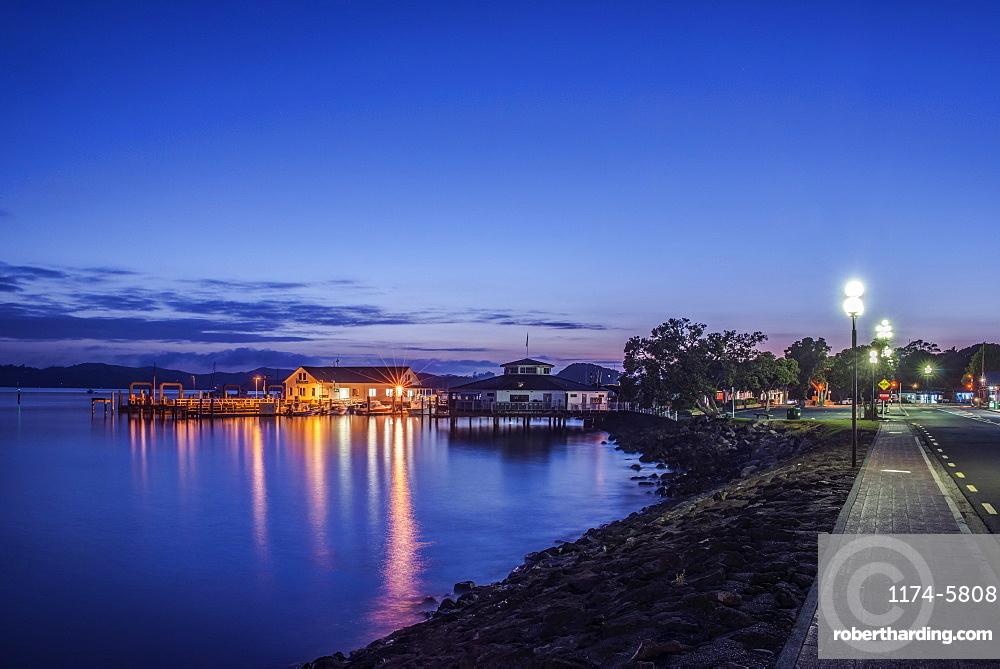 Illuminated buildings on water at dawn, Paihia, Paihia, New Zealand