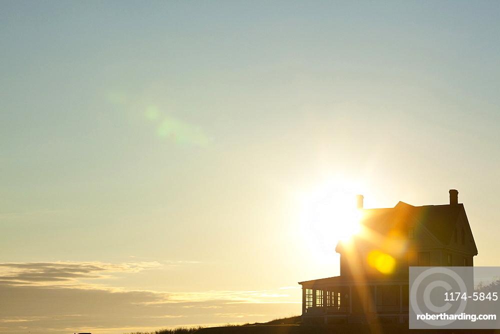 Sun shining behind rural house, Coupeville, Washington, USA