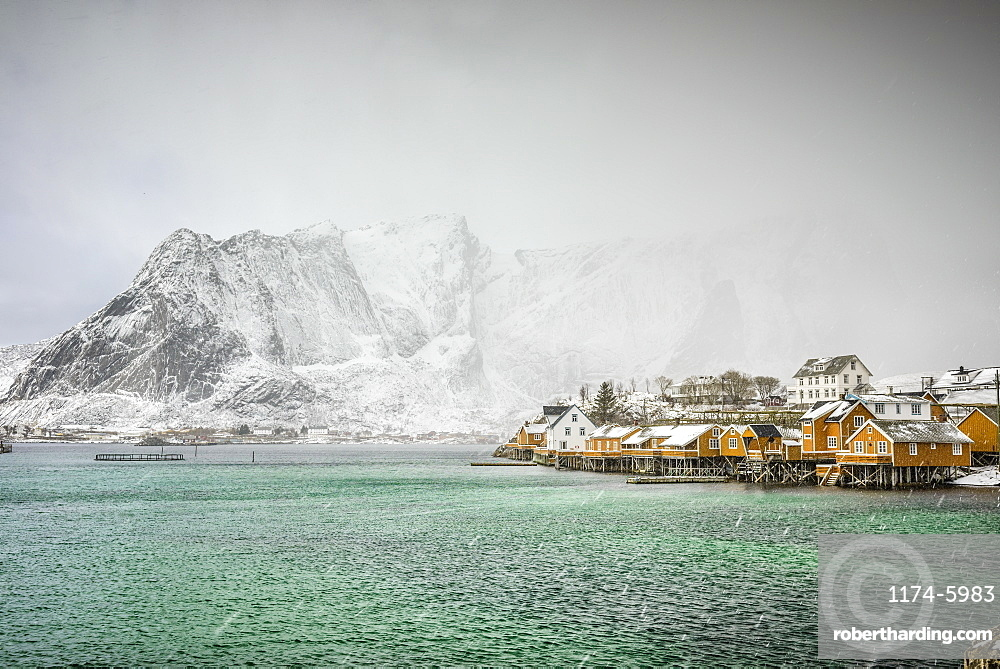 Snowy mountains overlooking rocky coastline, Reine, Lofoten Islands, Norway