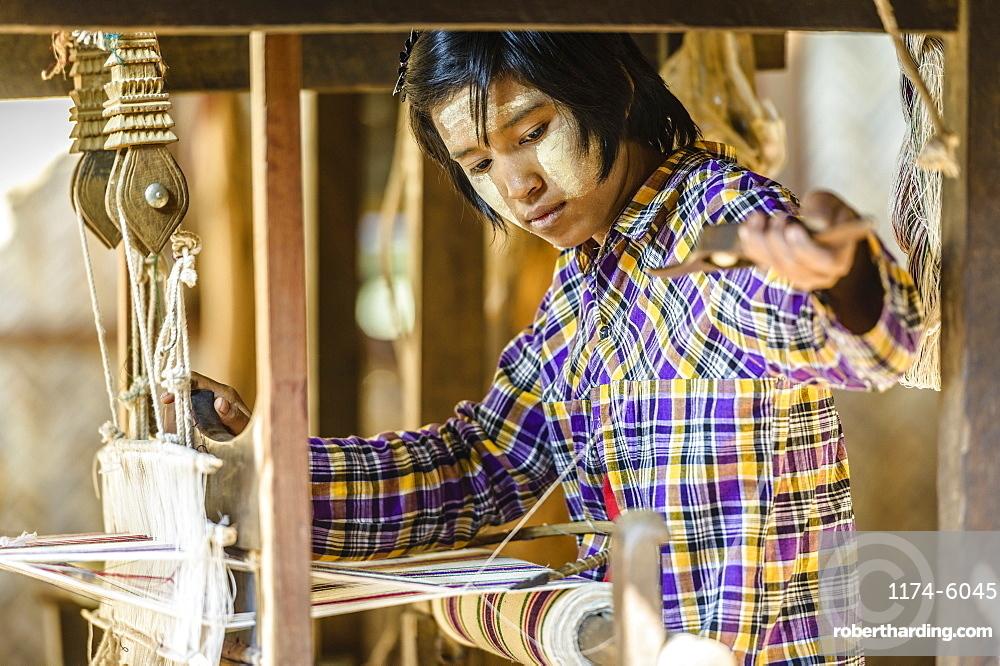 Asian girl weaving fabric