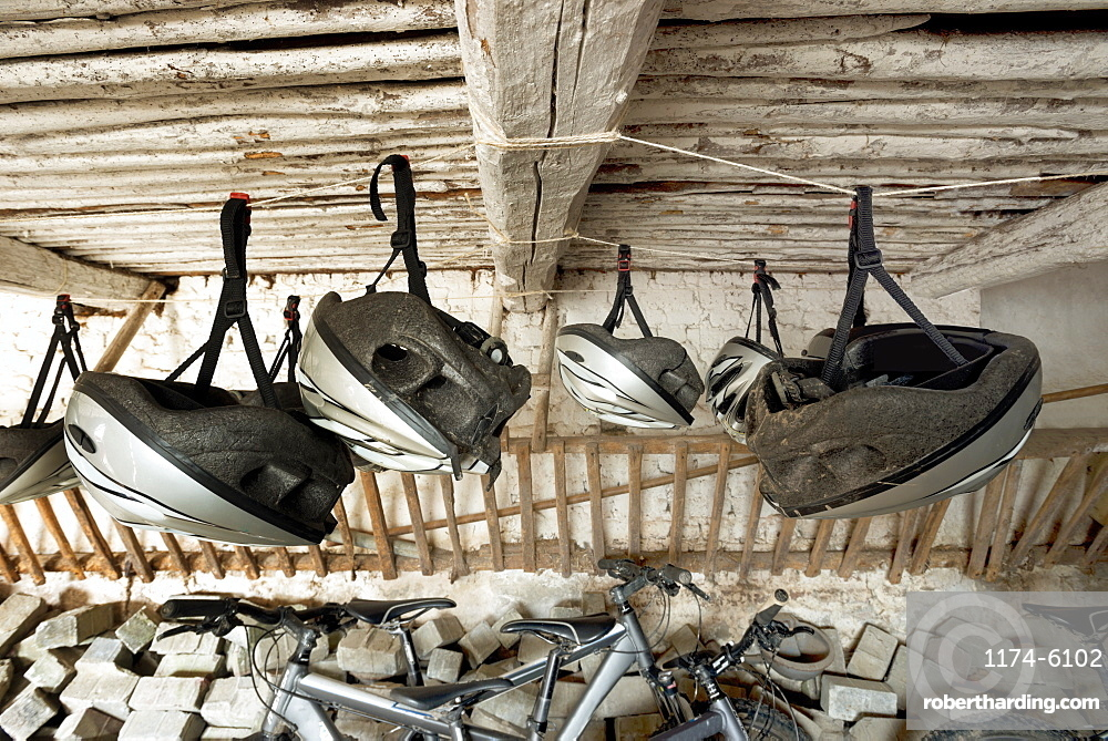 Bicycle helmets hanging from wooden ceiling