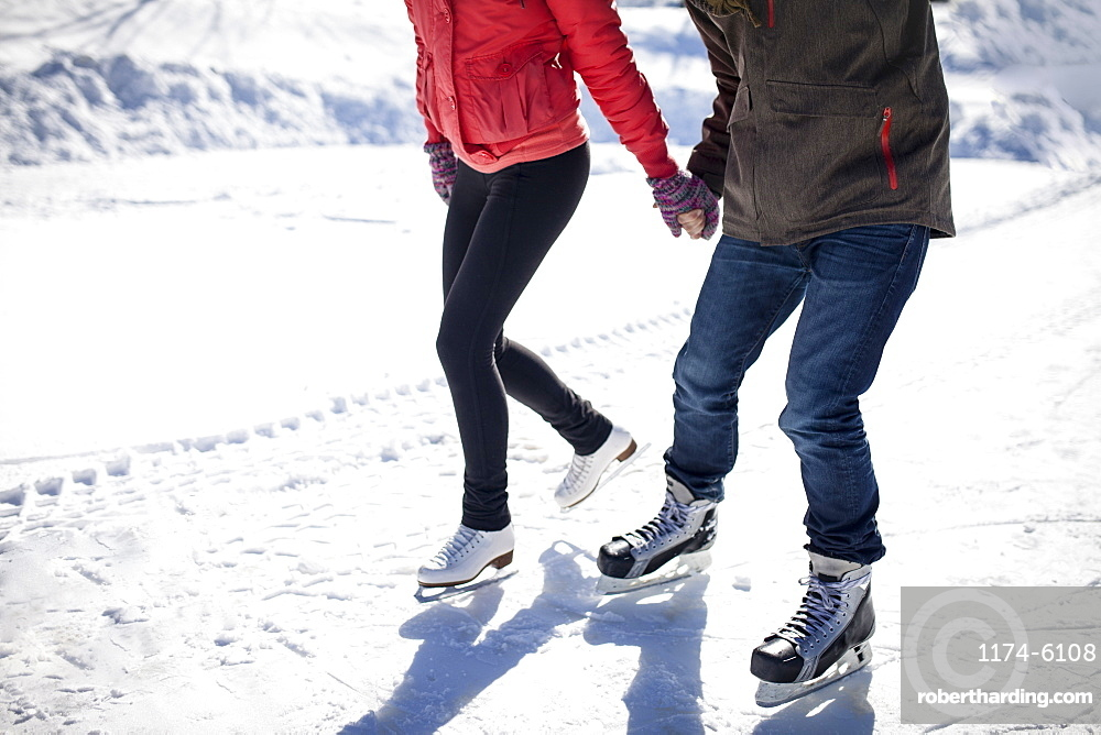 Caucasian couple ice skating on snowy frozen lake