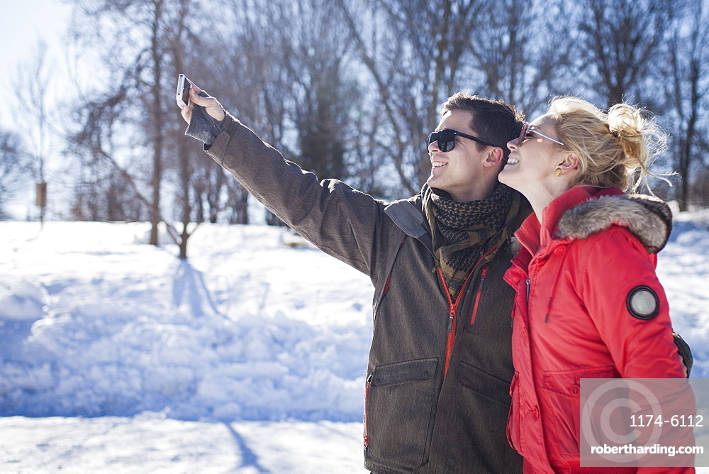 Caucasian couple taking cell phone selfie in winter