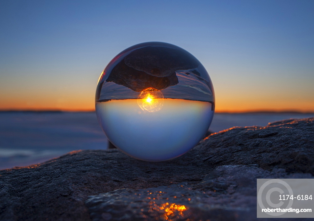 Close up of sunset horizon inverted in glass sphere