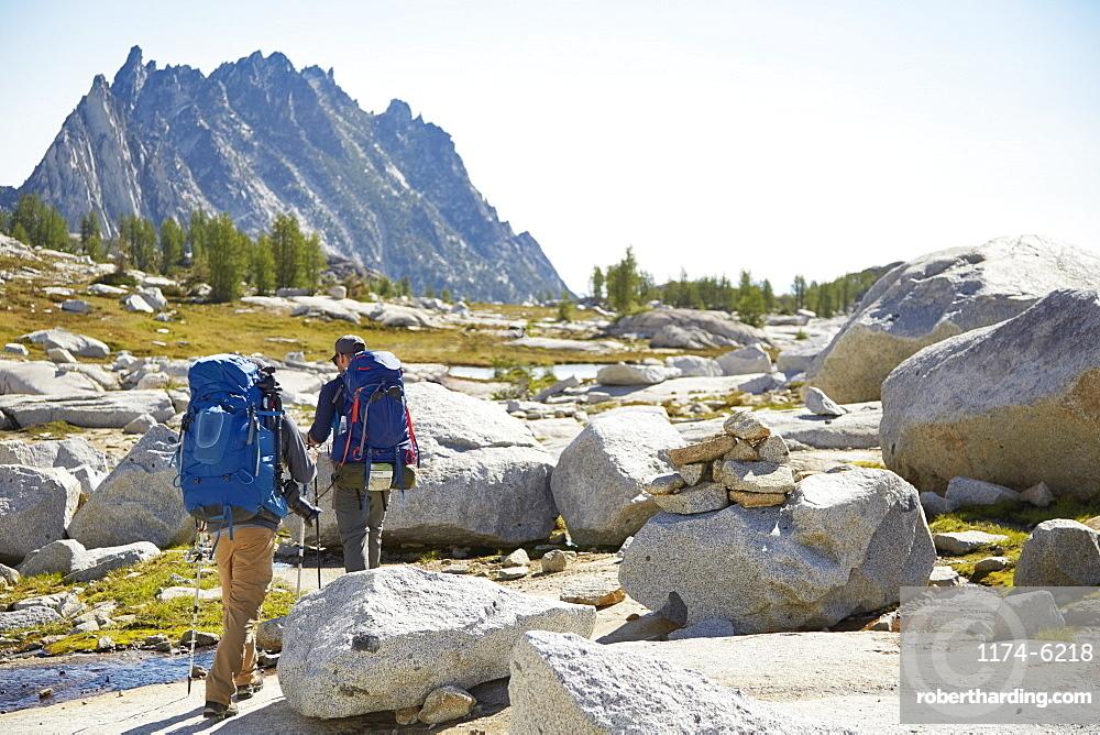 Hikers backpacking in rocky rural landscape, Leavenworth, Washington, USA