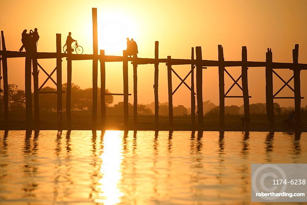 People walking on elevated wooden walkway at sunset, Myanmar, Burma