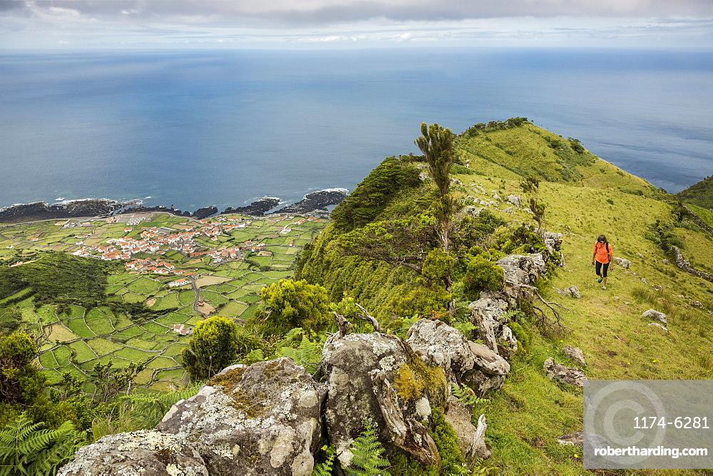 Hiker walking on hilltop path in rural landscape, Faja Grande, Flores, Portugal