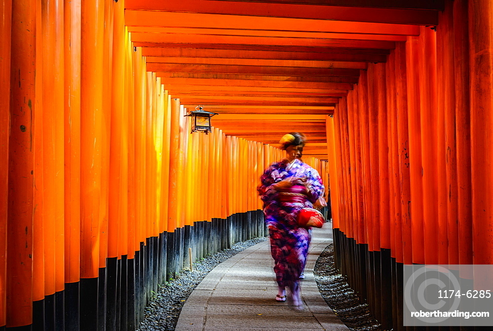 Woman in kimono walking under wooden pillars, Kyoto, Japan