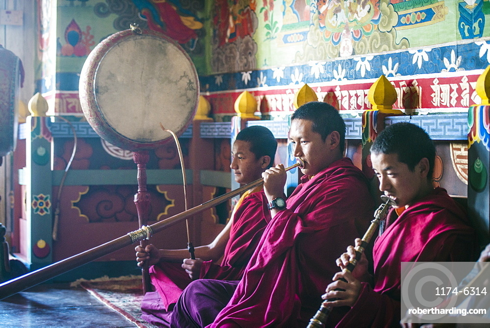 Asian monks playing instruments on temple floor, Bhutan, Kingdom of Bhutan