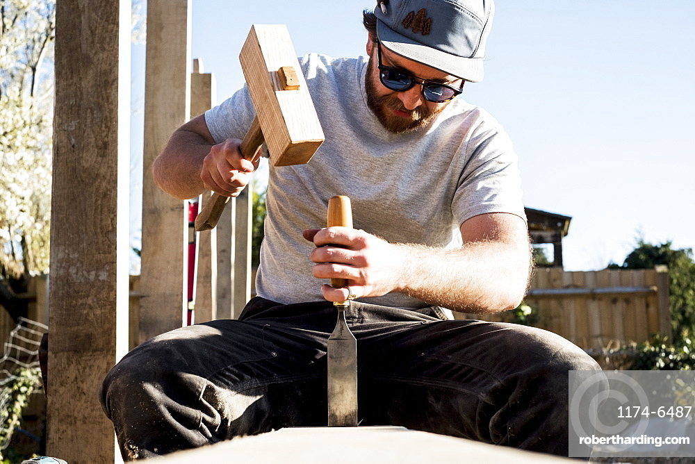Man wearing baseball cap and sunglasses on building site, using mallet and chisel, working on wooden beam, Oxfordshire, England