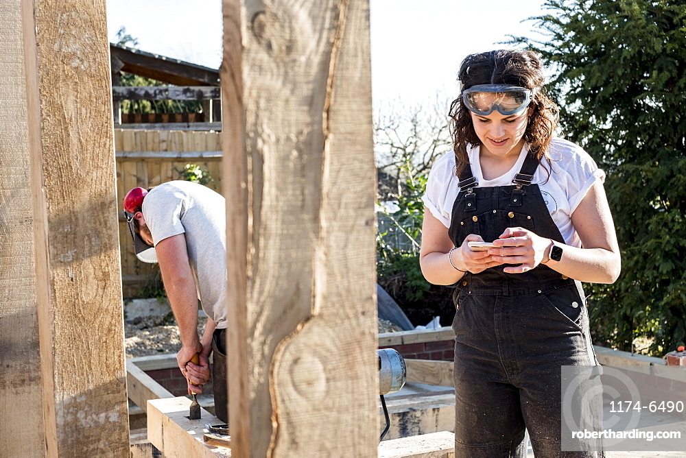 Smiling woman wearing dungarees and protective goggles standing on building site, checking her mobile phone, Oxfordshire, England