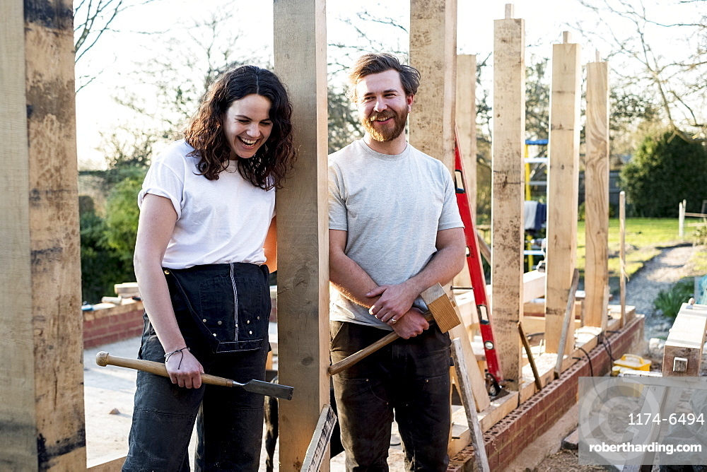 Smiling man and women holding hand tools standing on building site of residential building, Oxfordshire, England