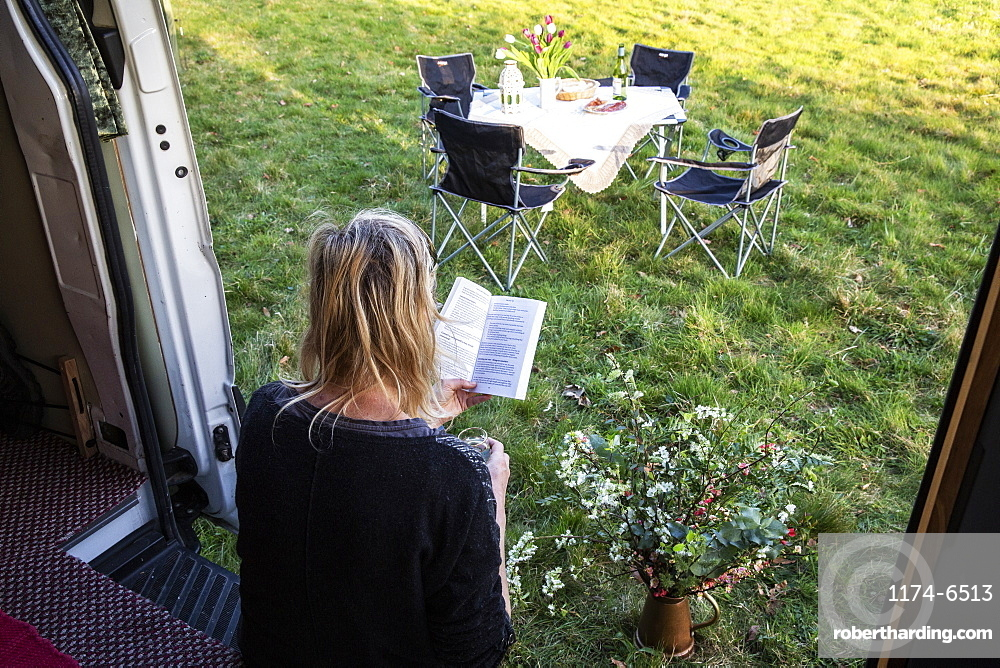 High angle rear view of woman sitting in door of camper van parked on a meadow, reading a book, Oxfordshire, England