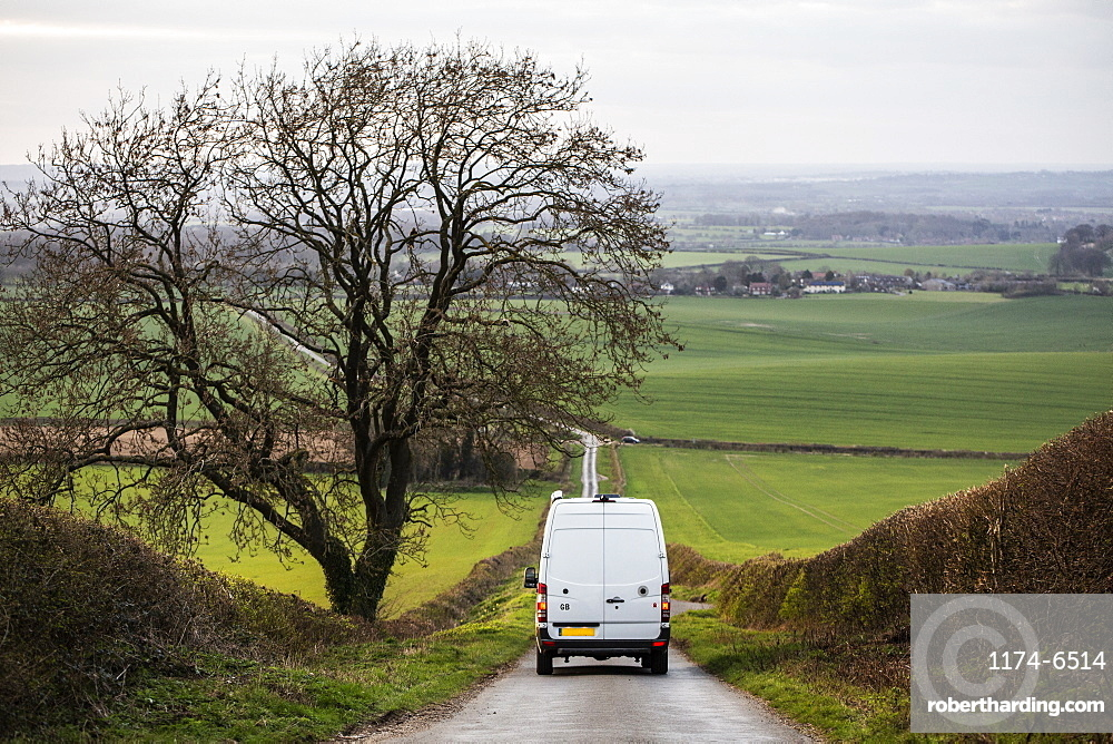 Rear view of camper van driving down a country lane, Oxfordshire, England