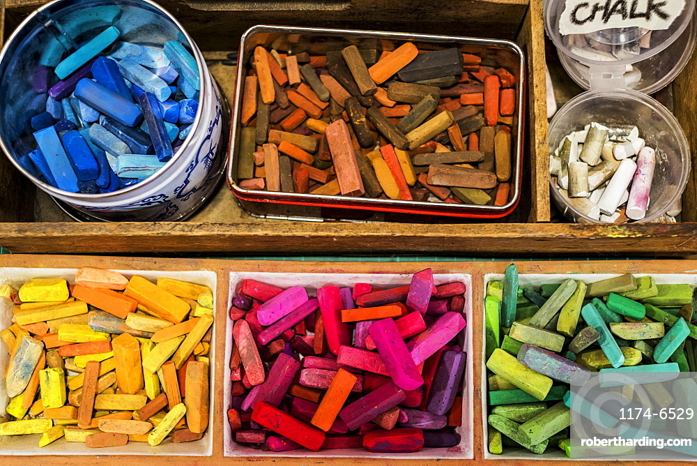 High angle close up of a wooden box with artist's crayons in a variety of vibrant colours, Oxfordshire, England
