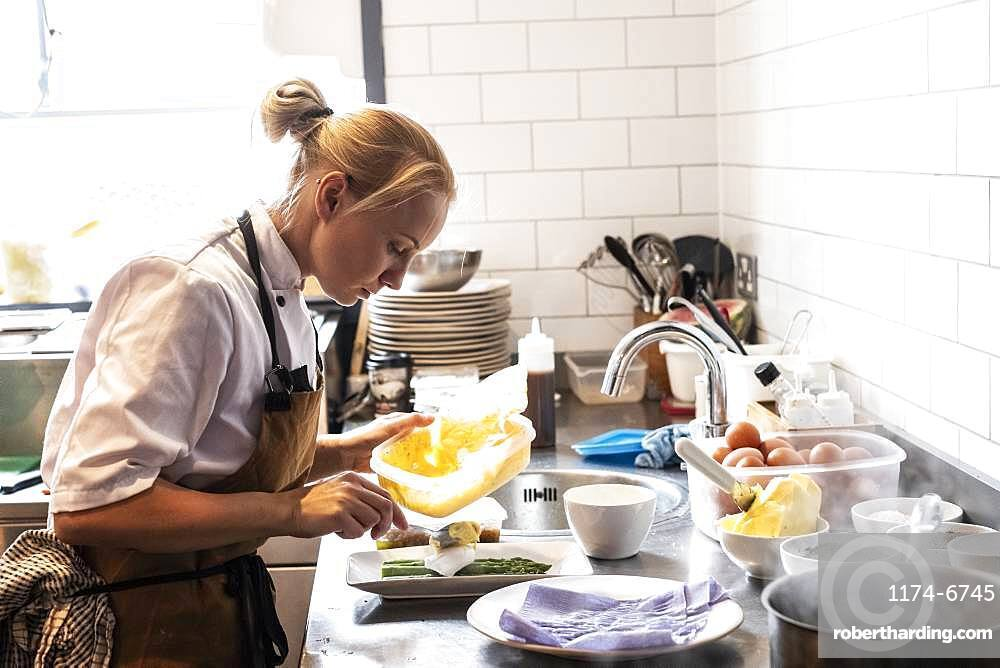 Female chef wearing brown apron standing at a kitchen counter, garnishing plate of asparagus