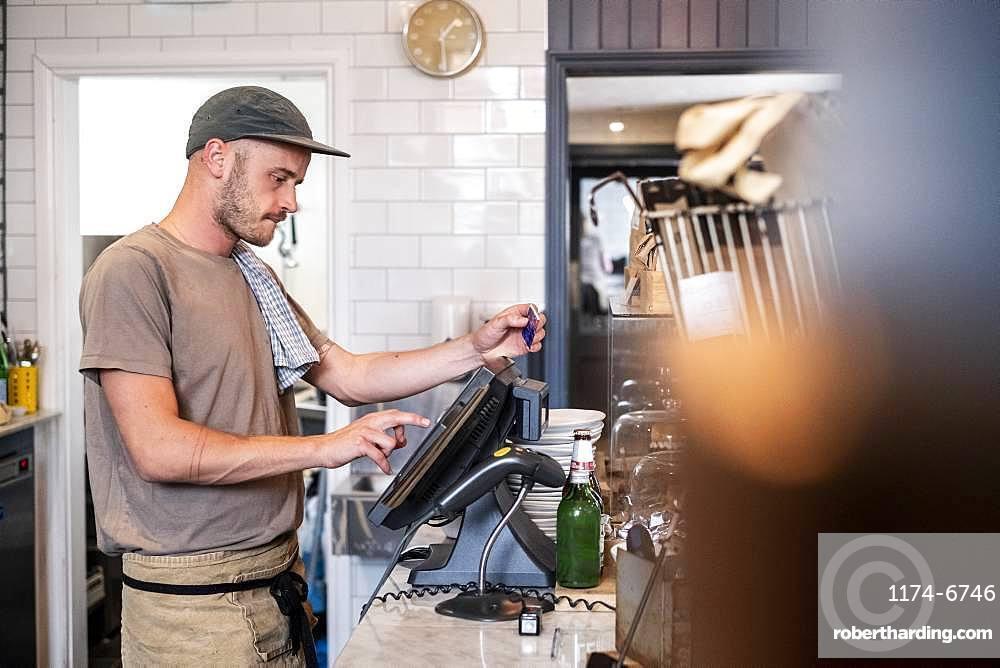 Bearded man wearing baseball cap standing at a till in a restaurant