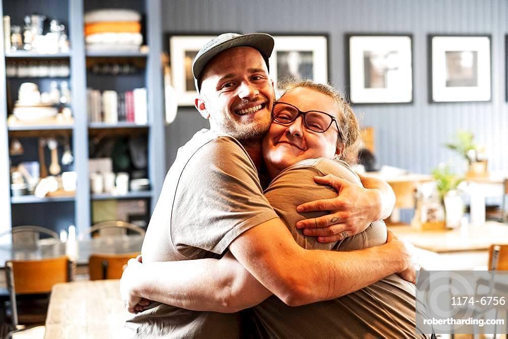 Man wearing baseball cap and woman wearing glasses hugging, smiling at camera