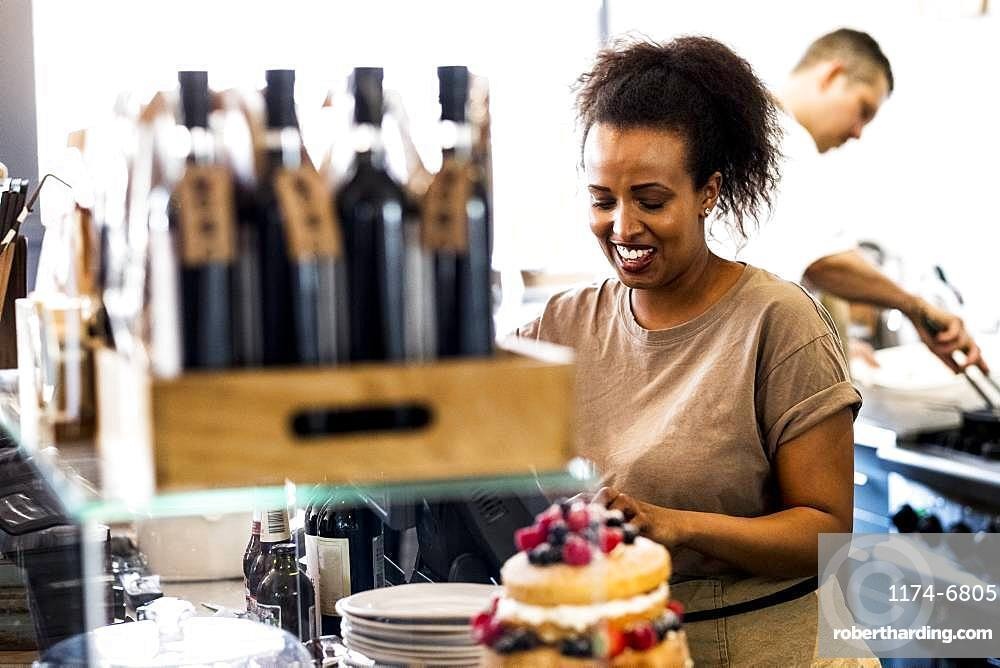 A woman working in a cafe, a stack of plates, and a layered sponge cake with fresh cream and fresh fruit