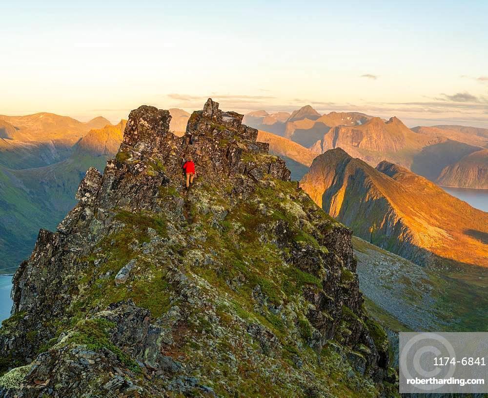 Man climbing up a steep peak in the jagged landscape of Senja Island, Troms, Senja Island, Lofoten Islands, Norway